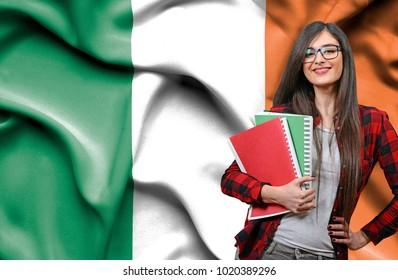 Happy female student holdimg books against national flag of Ireland