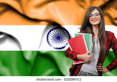 Happy female student holdimg books against national flag of India