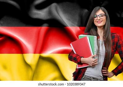 Happy female student holdimg books against national flag of Germany