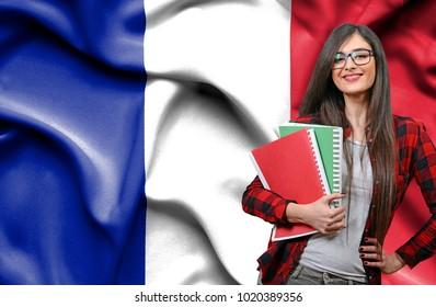 Happy female student holdimg books against national flag of France