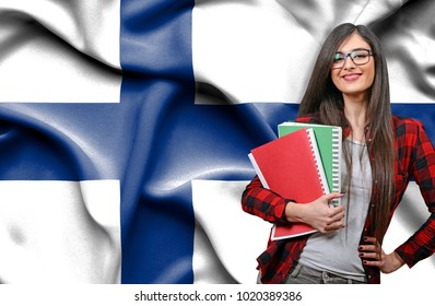 Happy female student holdimg books against national flag of Finland