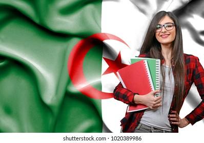 Happy female student holdimg books against national flag of Algeria