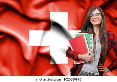 Happy female student holdimg books against national flag of Switzerland