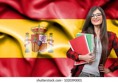 Happy female student holdimg books against national flag of Spain