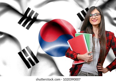 Happy female student holdimg books against national flag of South Korea