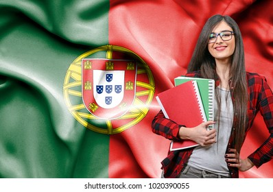 Happy female student holdimg books against national flag of Portugal