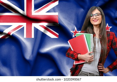 Happy female student holdimg books against national flag of New Zealand