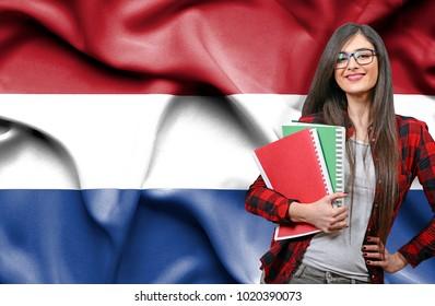 Happy female student holdimg books against national flag of Netherlands