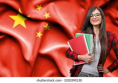 Happy female student holdimg books against national flag of China