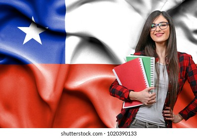 Happy female student holdimg books against national flag of Chile