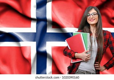 Happy female student holdimg books against national flag of Norway