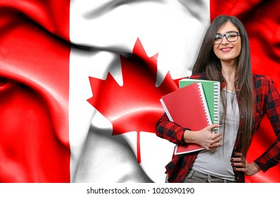 Happy female student holdimg books against national flag of Canada