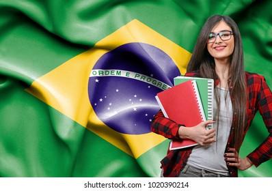 Happy female student holdimg books against national flag of Brazil