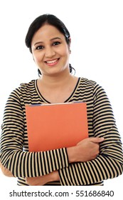 Happy female student holding text book