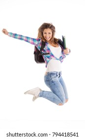 Happy female student jumping with her books and backpack while smiling and looking at the camera on white background