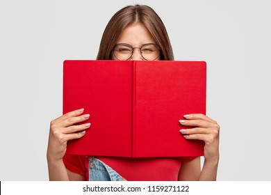 Happy female student laughs positively, wears round spectacles, hides behind red book, smiles as read something funny, poses against white background. People, youth, education and reading concept