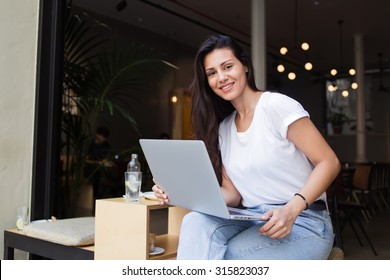 Happy female student posing for the camera while work on net-book and resting after lectures in coffee shop, smiling beautiful latin woman using laptop computer for remote work while sitting in cafe