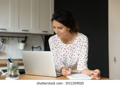 Happy female student sit at table at home look at laptop screen study distant making notes. Smiling young Caucasian woman work online on computer, watch webinar or take internet training course.