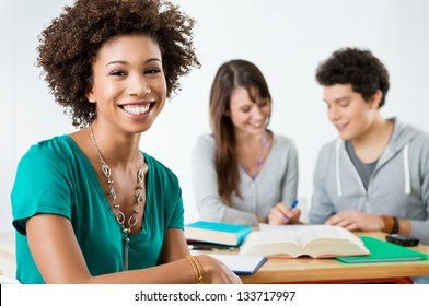 Happy Female Student Smiling And Looking At Camera In Class