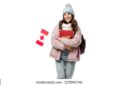 happy female student in winter clothes with canadian flag and notebooks isolated on white, studying abroad concept