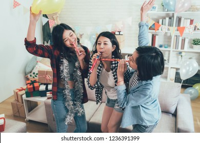 happy female students enjoy house party celebrating graduation playing with blowers. carefree girls dancing raising hands with toys and music in the cozy living room in decorated home.