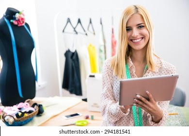 Happy female tailor holding tablet computer in workshop and looking at camera