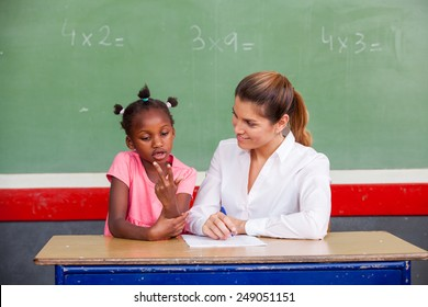 Happy female teacher and afro american schoolgirl discussing math questions in front of chalkboard.