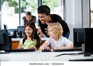 Happy female teacher assisting schoolchildren in using computer at school