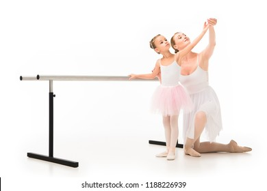 happy female teacher in tutu helping little ballerina exercising at ballet barre stand isolated on white background
