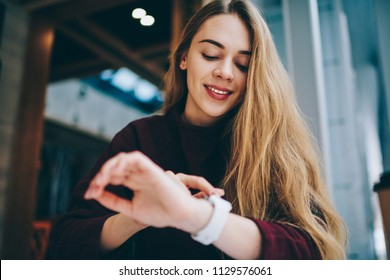 Happy female teenager checking notification on smartwatch and searching gps navigation while sitting at university campus, successful woman using wearable wristwatch for reading email indoors