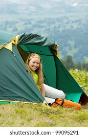 Happy female tourist in camp tent