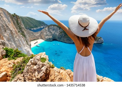 Happy female tourist enjoys the view to the famous shipwreck beach on Zakynthos island during her summer vacation time, Greece