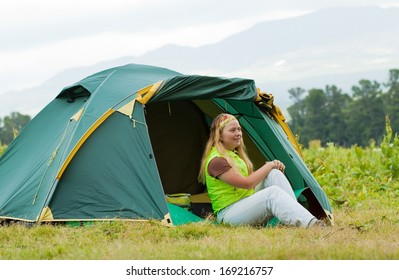 Happy female tourist in front camp tent