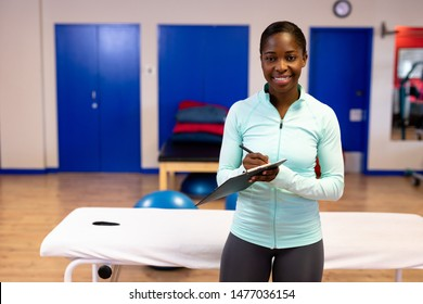 Happy female trainer looking at camera while writing on clipboard in sports center. Sports Rehab Centre with physiotherapists and patients working together towards healing