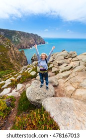 Happy female traveler standing on Cape Roca against the background of the Atlantic Ocean, Sintra, Portugal
