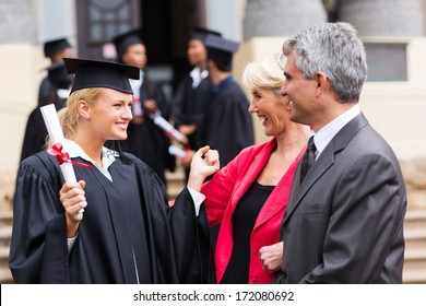 happy female university graduate with parents at graduation ceremony