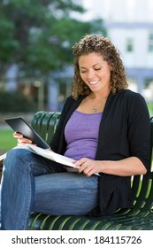 Happy female university student with digital tablet studying on bench at campus