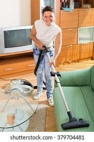 Happy female with vacuum cleaner smiling at living room do housework