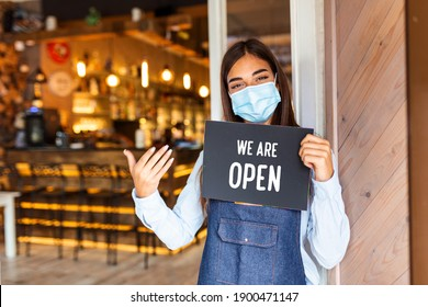 Happy female waitress with protective face mask holding open sign while standing at cafe or restaurant doorway, open again after lock down due to outbreak of coronavirus covid-19