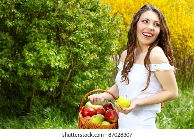 Happy Female in white dress presents basket of apples