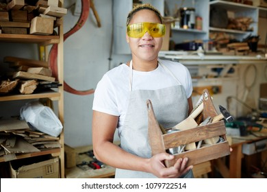 Happy female worker with wooden toolbox wearing protective eyeglasses during work