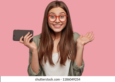 Happy female youngster with appealing look, positive emotions, clasps hands, has broad smile, satisfied as recieves unexpected invitation, holds modern cell phone, isolated over pink background.