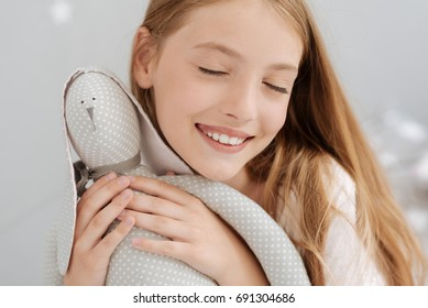 Happy female youngster embracing favorite toy