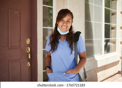 happy filipina nurse portrait in front of house