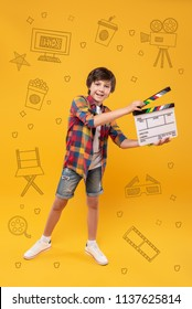 Happy filmmaker. Positive enthusiastic boy smiling and dreaming about becoming a filmmaker while holding a clapstick