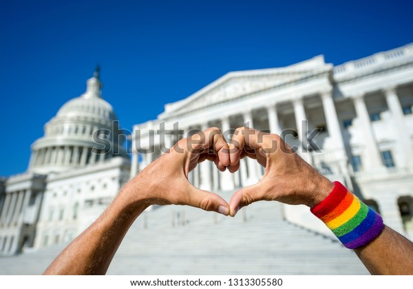 Happy fingers forming a hand heart on a bright sunny view of the Capitol Building in Washington, DC, USA