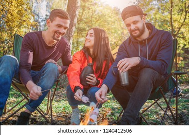 Happy firends sitting together and cooking murshmellow on fire. She looks at guy on left and laughing. Young men look at fire. Some of them have thermoses in hands.