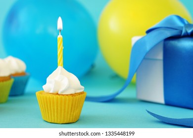 Happy first birthday party card with a mini cupcake, one yellow candle with flame, gift box with blue ribbon and colorful balloons on background.
