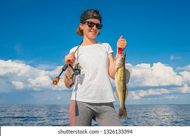 Happy fisher girl with walleye zander fish trophy at the boat