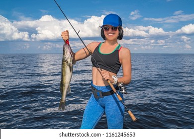 Happy fisher woman with zander walleye fish trophy at the boat